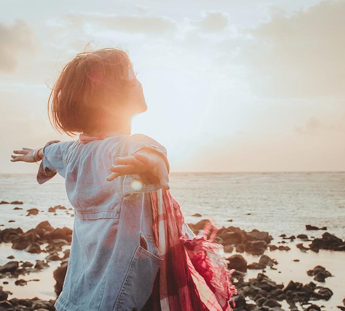 DM-Harmonics-Angstzustände-Frau streckt am Meer ihre Arme nach hinten und genießt ihre Freiheit