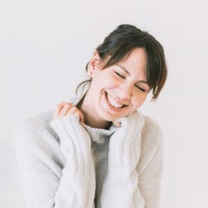 Dm-Harmonics-Glücklich sein-Frau im weißen Pullover freut sich