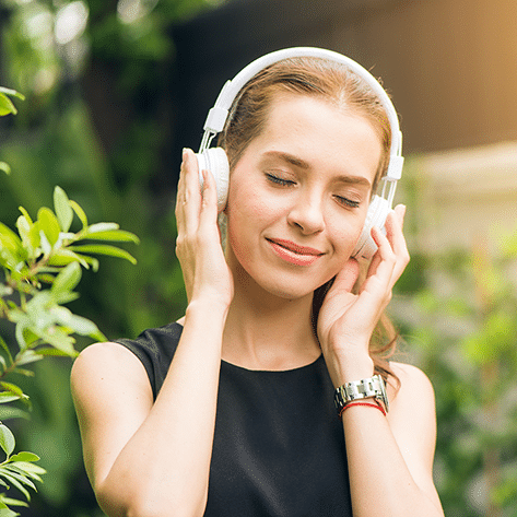 Frau hat Kopfhörer auf um binaurale Beats zu hören und um keine Probleme mehr zu haben